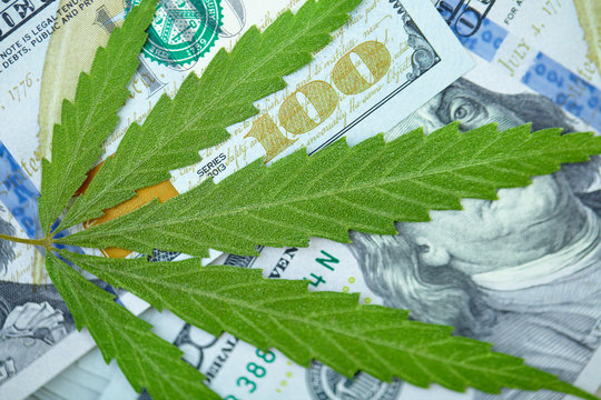 Cannabis leaf lies on top of American one hundred dollar bills, close up. Money from marijuana, hemp with money. Taxation and marijuana concept, weed tax