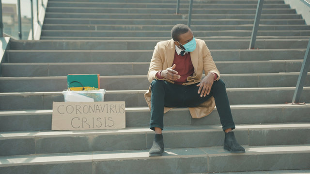 Unhappy young african american man wears mask sitting on stairs with box of personal stuff and poster with inscription Coronavirus Crisis got fired unemployed depression economy slow motion