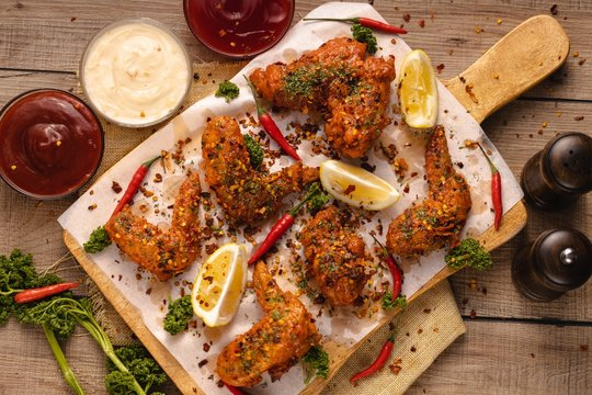High angle shot of delicious chicken wings with sauce, lemon and vegetables on the board