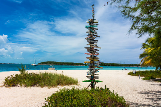 Great Exuma, Bahamas: view of the tropical beach of Stock Island with direction signs.