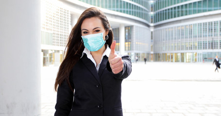 Confident young female manager outdoor in a modern urban setting giving thumbs up - coronavirus concept