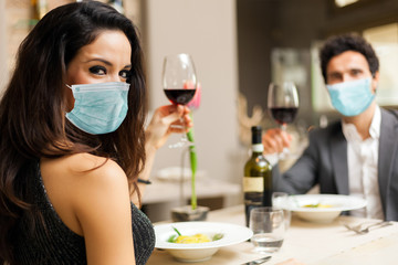 Couple toasting wineglasses in a luxury restaurant wearing a mask - coronavirus concept