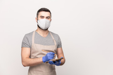 Young seious waiter in apron, protective mask and gloves writing down your order