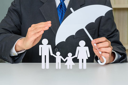 Businessman uses hands and an umbrella to protect family members e.g parents and two child