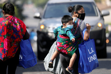 Families receive groceries from a Mother's Day food distribution in Los Angeles