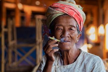Old lady of Pa O ethnic minority smoking a Burmese cigar at Indein Village near Inle Lake, Shan State, Myanmar (Burma).