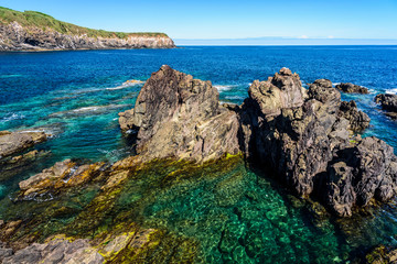 seascape in terceria. view of the rocky seaside in terceira with cliff in the background. seascape in azores, portugal.