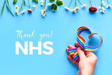 """Thank you NHS, doctors, nurses, medical teams and key workers, England and UK! Hand holding rainbow ribbon shaped as heart on blue mint background with flowers, trendy flat lay, text """"Thank you NHS""""."""