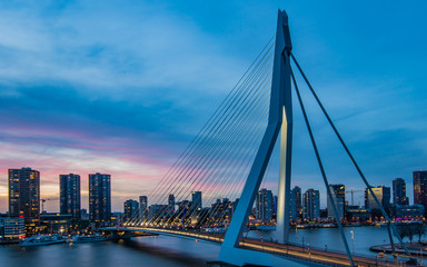 Long exposure shot at the Erasmus bridge in Rotterdam, the Nederlands, during the blue hour with a view over the beautiful skyscrapers.