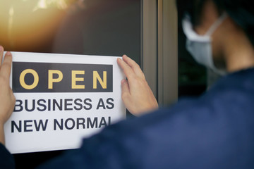 "Canvas Prints Countryside Reopening for business adapt to new normal in the novel Coronavirus COVID-19 pandemic. Rear view of business owner wearing medical mask placing open sign ""OPEN BUSINESS AS NEW NORMAL"" on front door."