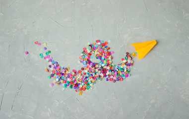a salute of paper colored confetti on a gray surface. Space for text. Minimalism of the great victory day in world war 2