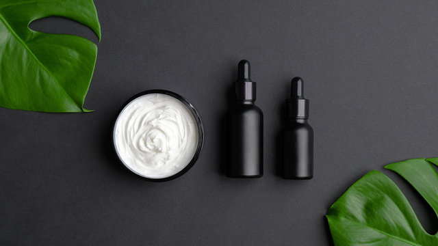 Set of luxury cosmetic products on black background top view. Flat lay natural body cream, black clean dropper bottles mockup and tropical monstera leaves. SPA natural organic beauty products.