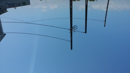 Obraz Low Angle View Of Bike In Power Lines Against Blue Sky - fototapety do salonu