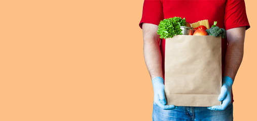 Grocery delivery courier man in red uniform and medical gloves holds paper bag with food on orange background. Safe food delivery during quarantine, online shopping or donation concept. Copy space.