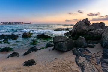 dramatic sunset on the sea. waves crashing rocks on sandy beach. beautiful cloudscape above the horizon line