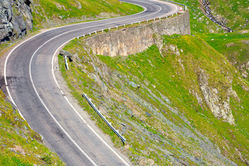 winding mountain road on a sunny day. empty highway run through valley.  great european journey in summertime concept.