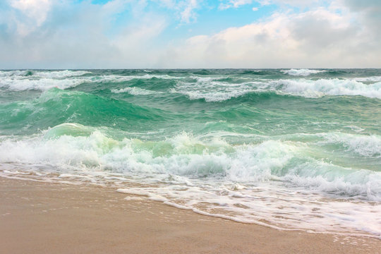 storm on the sandy shore. dramatic ocean scenery with cloudy sky. rough water and crashing waves