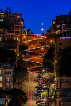 High angle view of illuminated homes on Lombard Street in San Francisco, California at sunset with car light trails