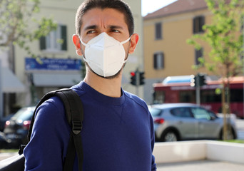 COVID-19 Pandemic Coronavirus Man in city street wearing KN95 FFP2 face mask protective for spreading of Coronavirus Disease 2019. Portrait of man with face mask against SARS-CoV-2.