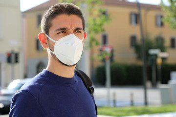 COVID-19 Pandemic Coronavirus Man in city street wearing KN95 FFP2 face mask protective for...