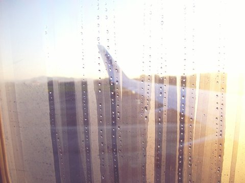 Airplane Wing At Airport Runway Seen From Wet Window