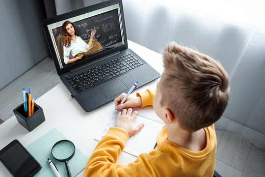 Distance learning, a boy learns math while looking at a laptop beech during an online lesson. The concept of online education, home education, technology, quarantine, self-isolation.