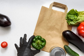 Vegetables, red and green peppers, eggplant, cucumber, canned food, lettuce and a rubber glove lie on a paper bag on isolated background. Top view copy space. Donation. contactless food delivery.