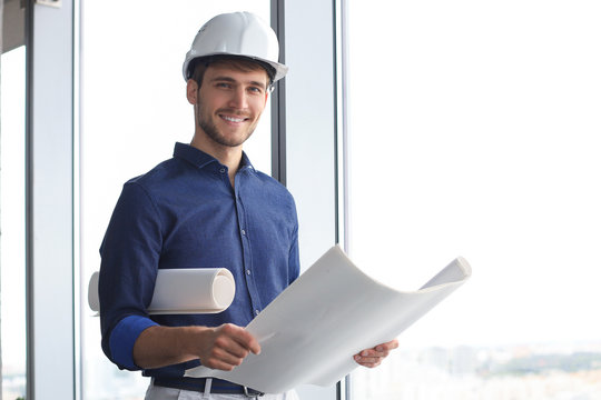 Shot of male architect wearing hardhat and inspecting new building.