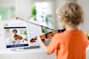 Child playing violin. Remote learning.