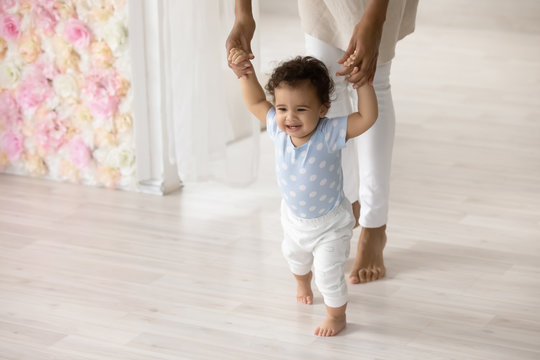 Smiling little biracial toddler infant child make first steps at home holding mom hands, happy small african American baby learn walking with mother support and care, upbringing, childcare concept