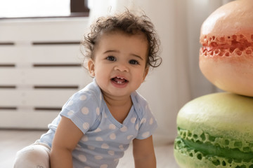 Keuken foto achterwand Hoogte schaal Portrait of cute little african American toddler infant sit on floor at home have fun playing, smiling small biracial baby child in organic natural clothes look at camera posing, childcare concept