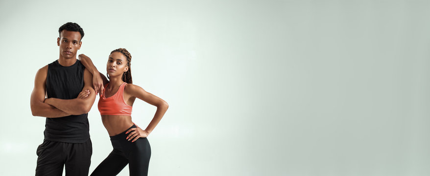 Working out together. Young african fitness couple in sportswear looking at camera while standing against grey background
