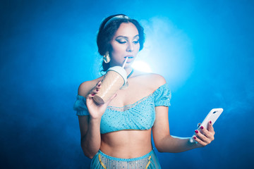 Magic, cosplay and fairy tale concept - Portrait of a young woman in the image of an Eastern fairy Princess holds smartphone and shaker on blue background.