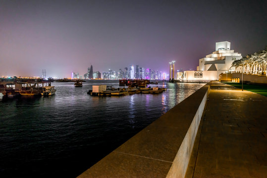 Visit of Qatar Museum of Islamic Art  in Doha mirroring in water of pond at night. Futuristic architecture near the bay of Doha.