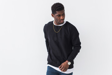 Street fashion concept - Studio shot of young handsome African man wearing sweatshirt against white...