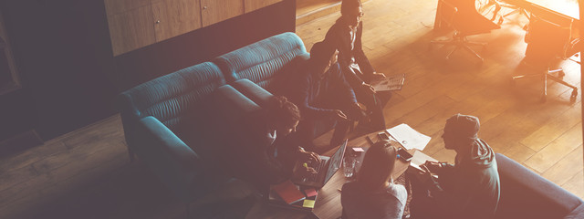 Startup team brainstorming. Meeting on the couch. loft office. Five people. Intentional sun glare. Wide screen, panoramic