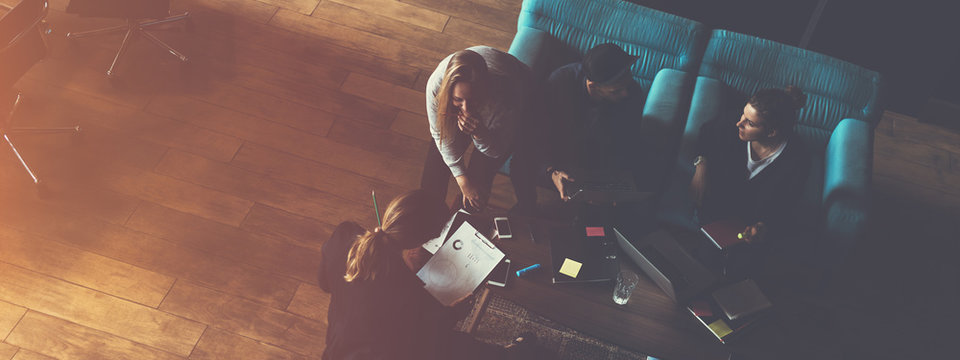 Business group researching new plan. Team meeting on the couch. Big open space office. Five people. Top view. Wide screen, panoramic