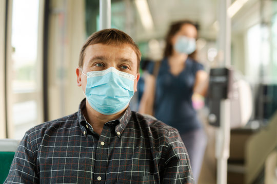 Passenger in disposable mask in city streetcar
