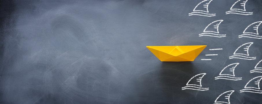 concept banner of avoiding crisis. paper boat escaping sharks idea