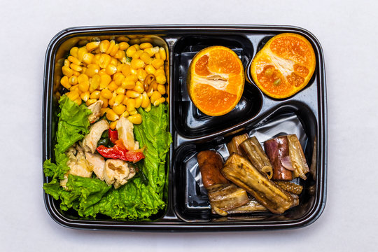 Healthy diet meal plan with corn, shredded chicken, veggies and oranges in bento box top view