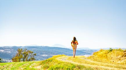Fotoväggar - Frau beim Spaziergang auf einem Feldweg