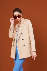 High fashion portrait of young elegant woman in beige jacket and jeans.
