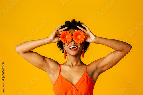Portrait of a an excited young woman with orange gerbera daisies covering her eyes