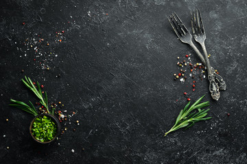 Fototapete - Black cooking background. Rosemary and spices on a black stone table. Top view. Free space for your text.