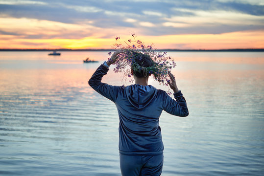 A woman with a wreath of wildflowers on the shore of a lake.An evening at Saint John's Eve by the lake.