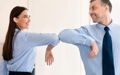 Keuken foto achterwand Hoogte schaal Businesswoman And Businessman Bumping Elbows Standing In Office