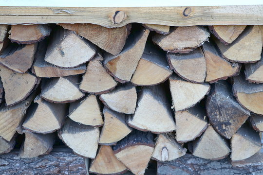Pile of dry firewood as closeup, stacked logs of wood