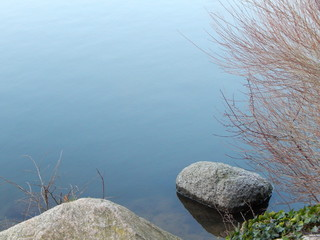 Lakeshore with little rocks in the blue water as background with copy space