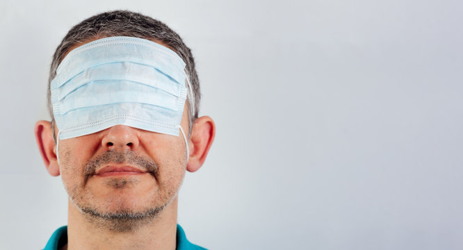 isolated blindfolded man with surgical mask over the eyes and bare mouth and nose