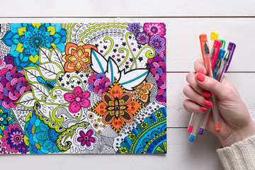 Adult coloring book, stress relieving trend. Art therapy, mental health, creativity and mindfulness concept. Flat lay close up on woman hands coloring an adult coloring book background.